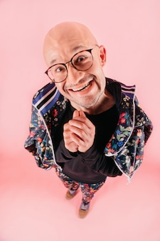 Funny portrait from above of  bald man in glasses shows  facial expression.