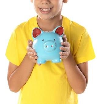 Funny portrait of little boy holding a blue moneybox isolated on a white background.