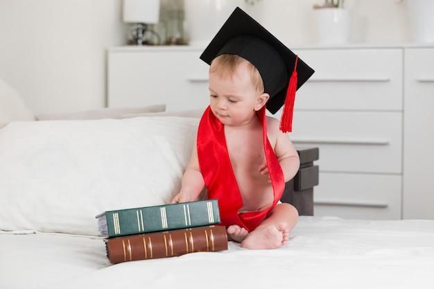큰 책을보고 졸업 모자에 10 개월 아기의 재미있는 초상화 프리미엄 사진