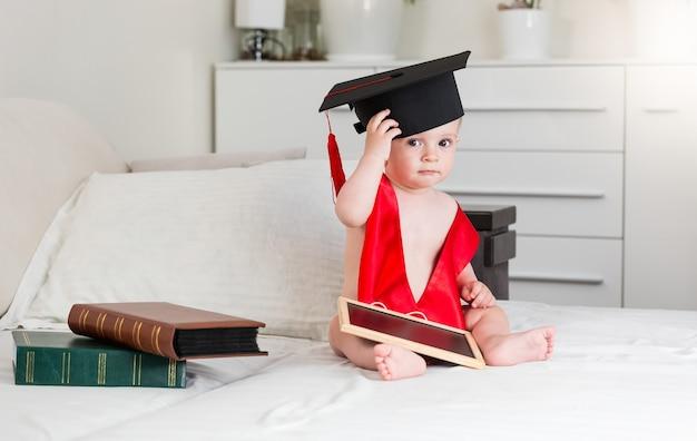 Забавный портрет 10-месячного мальчика с книгами в выпускной кепке