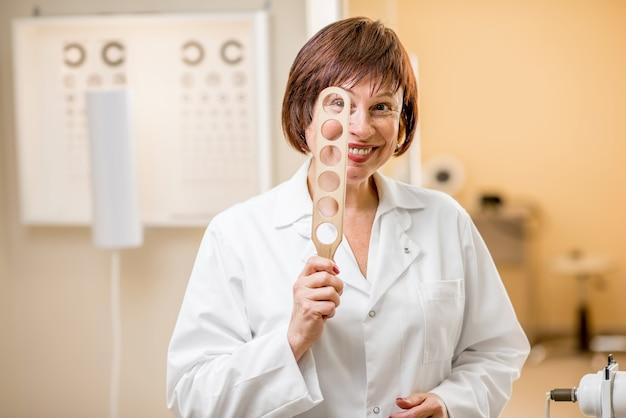 オフィスで視力検査のためのレンズを持って立っている年配の女性眼科医の面白い肖像画