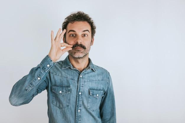 Забавный портрет коричневого улыбающегося красавца, касающегося его усов джинсовая рубашка серый фон копирование пространства