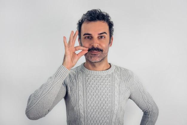 Забавный портрет коричневого, улыбающегося красивого мужчины, касающегося его усов с серым свитером. серый фон.