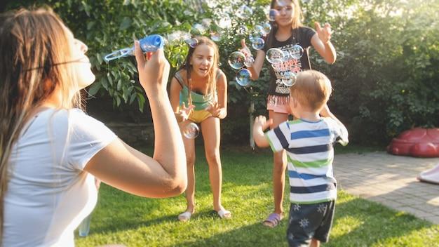 Забавный портрет счастливой веселой молодой семьи, дующей мыльные пузыри в саду на заднем дворе дома