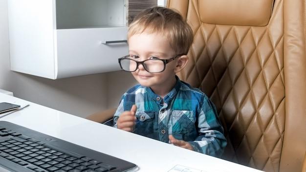 コンピューターのオフィスで働いている眼鏡をかけている少年の面白い肖像画。