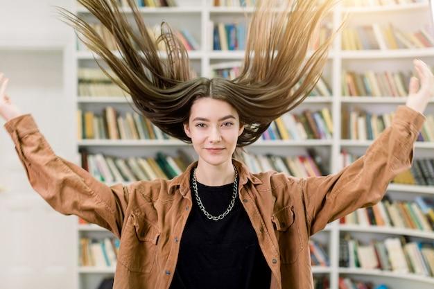 예쁜 갈색 머리 젊은 백인 여자, 학생, 갈색 캐주얼 셔츠에 재미 있은 초상화, 그녀의 긴 스트레이트 머리를 던지고 도서관의 책 선반 인테리어에 포즈