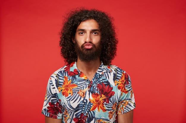 우스꽝스러운 얼굴을 만드는 수염을 가진 젊은 검은 머리 곱슬 남자의 재미있는 초상화, 멀티 컬러 꽃 셔츠를 입고