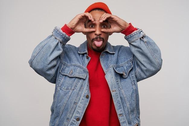 Ritratto divertente del maschio dalla pelle scura piuttosto giovane barbuto che mostra la lingua e che fa le facce ridicole mentre levandosi in piedi sul bianco in cappello rosso, pullon rosso e cappotto dei jeans