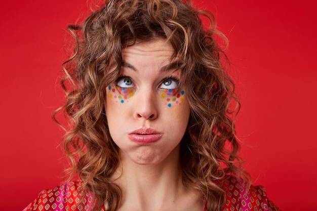 Funny portrait of pretty young female with curly hair and festive makeup looking upwards and blowing on her hair, making fun while posing, wearing motley patterned top