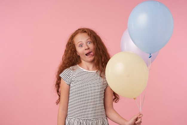 Funny portrait of redhead curly female kid in striped dress standing over pink background with air balloons, celebrating holday, showing tongue and making faces