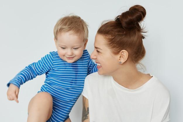 Ritratto divertente del bambino e della giovane madre felice con il mazzo di capelli castani che esaminano il suo maschiaccio. giovane donna europea sorridente che fissa il figlio con enorme amore. concetto di stile di vita familiare positivo.