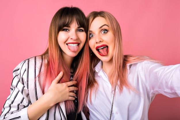 Un ritratto divertente di due ragazze sorprese felici che si divertono insieme e che spettegolano, vestiti di eredità in bianco e nero