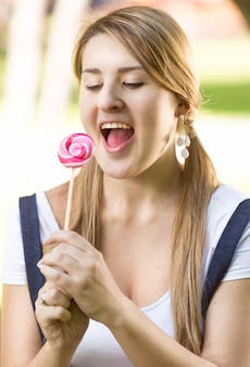 Funny portrait of woman with pigtails looking at red lollipop