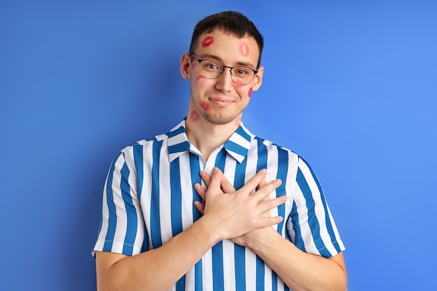 Funny portrait of young caucasian nerd with kiss imprints isolated on blue background