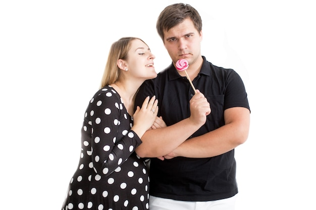 Funny portrait of young couple posing with lollipop