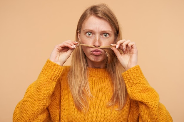 Funny portrait of young green-eyed redhead woman imitating mustache with lock of hair and looking excitedly, isolated on beige in mustard sweater