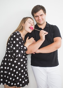 Funny portrait of young man holding lollipop and giving in to girlfriend