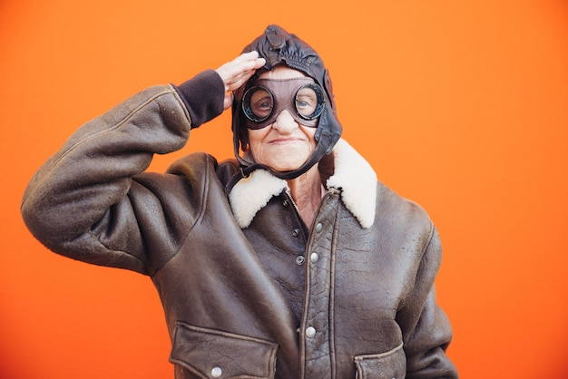 Funny portraits with old grandmother. senior woman acting as an aviator from the first world war