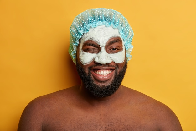 Funny positive dark skinned man winks eyes, applies antiaging facial clay mask after taking shower, wears protective headgear
