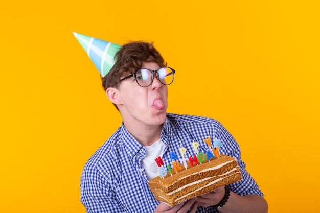 Funny positive guy in glasses holds in his hands a cake with the inscription happy birthday posing on a yellow wall.