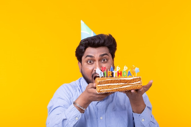 Funny positive guy holds in his hands a homemade cake with the inscription happy birthday posing on