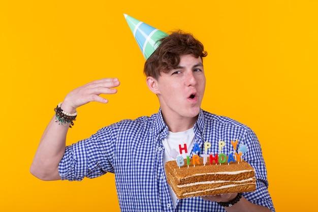 おかしいポジティブな男は、お誕生日おめでとうの碑文がポーズをとって自家製ケーキを手に持っています