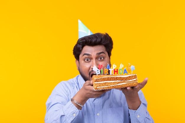 おかしいポジティブな男は、お誕生日おめでとうの碑文のポーズで自家製ケーキを手に持っています