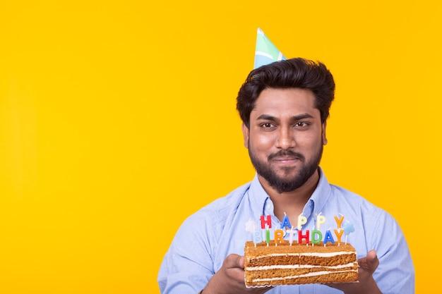 メガネの面白いポジティブな男は、黄色の壁にポーズをとってお誕生日おめでとうの碑文とケーキを手に持っています。休日や記念日の概念。