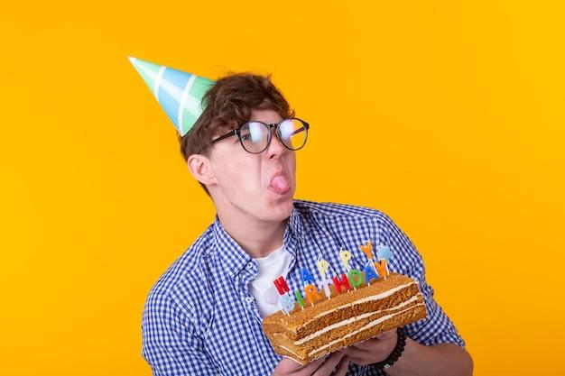 眼鏡をかけた面白いポジティブな男は、黄色の壁にポーズをとってお誕生日おめでとうの碑文とケーキを手に持っています。