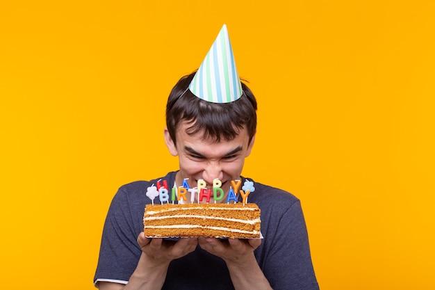 眼鏡の面白い前向きな男は、彼の手に碑文お誕生日おめでとうと自家製ケーキを保持