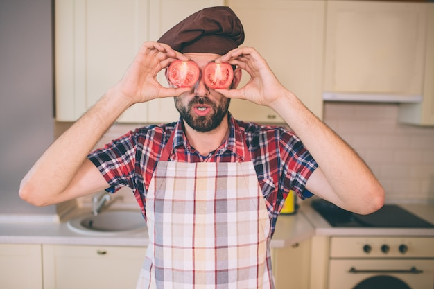 Funny and positive guy stands and holds pieces of tomato in hands. he covers eyes. bearded man has wondered look. guy wears pron.