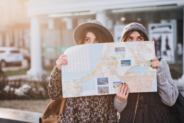 Funny positive image of fashionable women on sunny street having fun in city, hiding behind the citymap. travelling together, best friends, get a lost in big city, true emotions.