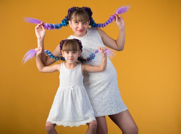 黄色の壁でポーズをとる色の三つ編みと同じ白いサンドレスの面白いポジティブなママと娘。補充を待っている面白い創造的な家族の概念。コピースペース