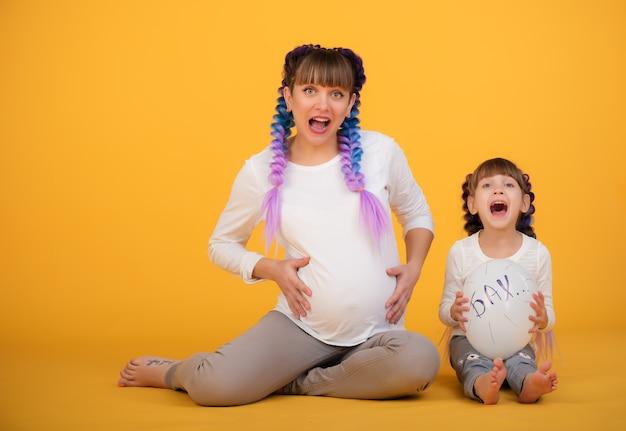 面白いポジティブなママと娘は、黄色い壁にポーズをとっている妊娠中の腹を示しています。愚かさと家族の遊びの概念。コピースペース