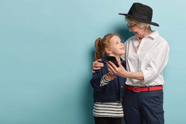 面白いポジティブな老婆は小さな孫娘を抱きしめ、現代の携帯電話で写真を撮り、自分撮りを楽しんで、お互いを見て、テクノロジーを使います。家族、ライフスタイル、関係の概念
