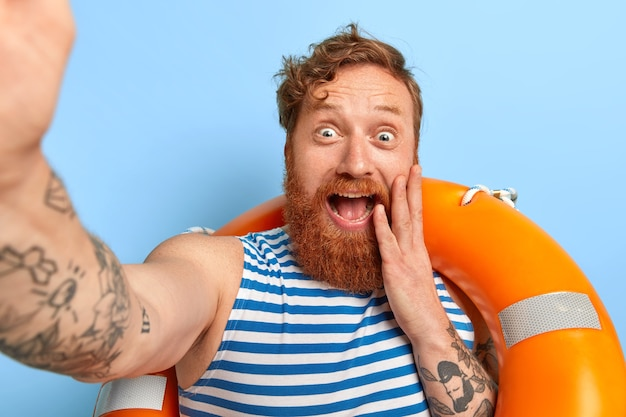 面白いポジティブな赤毛の男は自分の写真を撮り、屋内で膨らんだ救命浮輪を持って立って、セーラーベストを着て、厚いひげを生やして、ビーチで素晴らしい休暇を楽しんでいます