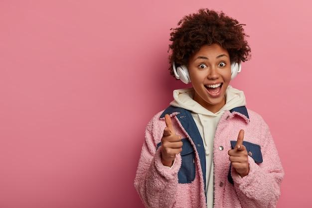 面白いポジティブな女性は冗談を言って、指を指して、良い気分を表現します