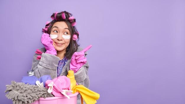 La giovane donna asiatica positiva divertente posa vicino al cesto della biancheria pesante indossa la vestaglia e i guanti di gomma indica via sullo spazio della copia subisce trattamenti di bellezza isolati sul muro viola