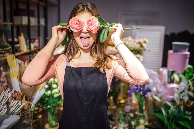 Funny and positive young female florist cover eyes with roses and show tongue. she has fun. plants and flowers stand in vases behind.