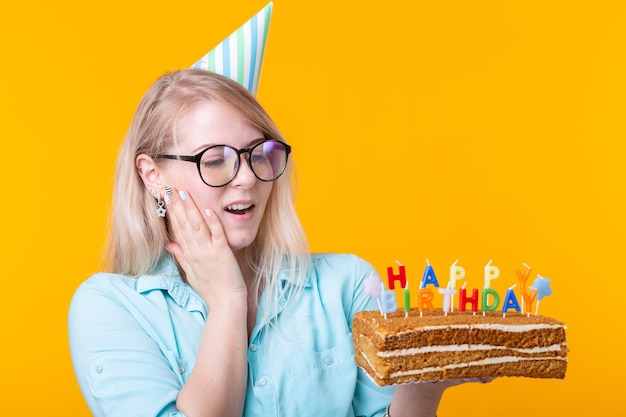 Funny positive young woman holds in her hands a homemade cake with the inscription happy birthday posing on a yellow wall. concept of holidays and anniversaries.