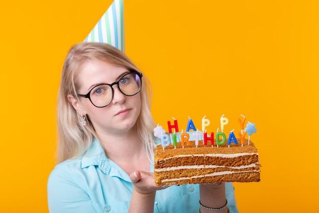 おかしいポジティブな若い女性は、お誕生日おめでとうの碑文と自家製ケーキを手に持っています