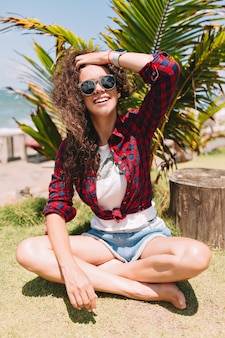 Divertente donna abbastanza affascinante con vere emozioni felici riposa sul prato con palme e si diverte. vacanze estive