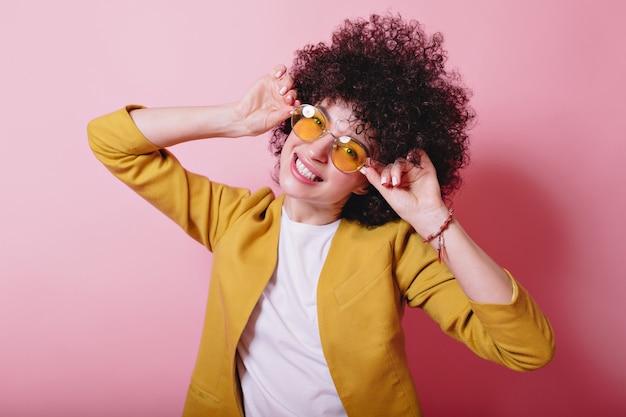 노란색 재킷과 노란색 안경을 입은 사랑스러운 고리가있는 재미있는 예쁜 아가씨는 분홍색에 재미 있습니다.