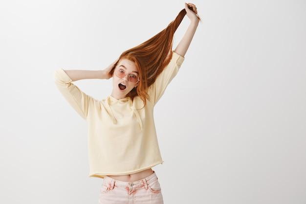 Смешная симпатичная рыжая девушка тянет за волосы и кричит