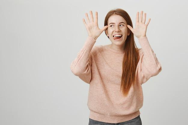 面白いかなり赤毛の女性aping、友達をからかって、笑顔