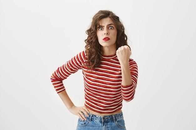 La bella donna divertente ti minaccia con il pugno, rimproverandoti o avvisandoti