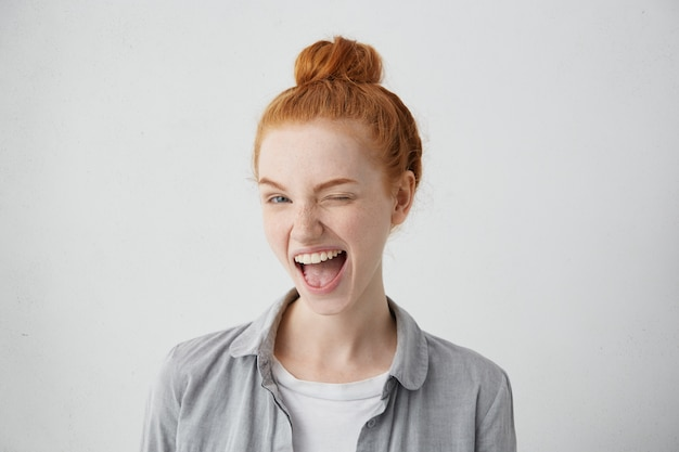 Funny red-haired female teenager with bun wearing casual shirt having joyful expression closing one of her eyes with pleasure and opening widely mouth having broad smile isolated