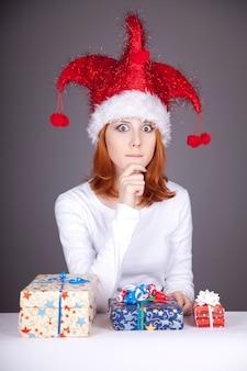 ギフトボックスとクリスマスキャップの面白い赤毛の女の子。