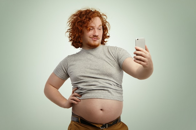 Funny red-haired overweight male trying to look attractive and sexy, holding hand on his waist while taking selfie with electronic device, belt on his pants in undone because of fat belly sticking out