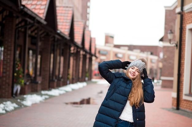 キエフの路上でポーズをとって黒い冬のコートとニット帽を身に着けている面白い赤い髪の若い女性